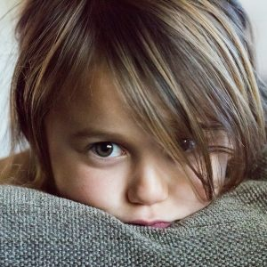 a child staring into the camera with their head on a pillow
