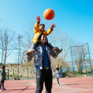 a father with his son on his shoulders tossing a basketball