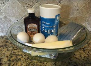 butter, cream cheese, eggs, sugar, and vanilla extract all sitting in a bowl