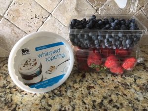 cartons of blueberries and strawberries sitting next to whipped cream