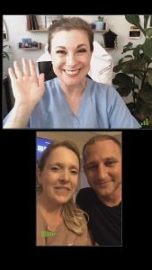 A picture of a zoom call with a lady on top waving and smiling and a couple on the bottom smiling