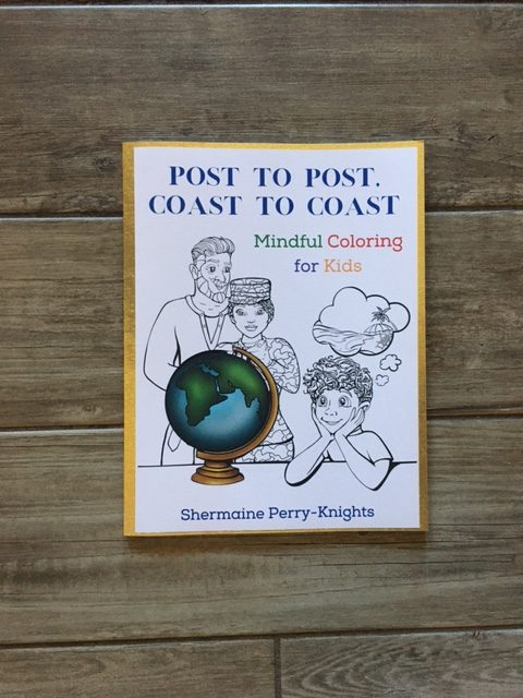 """the coloring book """"Post to Post, Coast to Coast"""" sitting on a wooden table"""