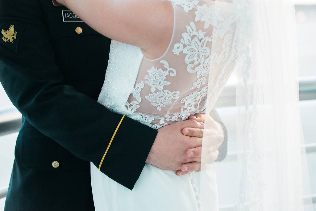a woman in a wedding dress and her husband with his hands behind her back
