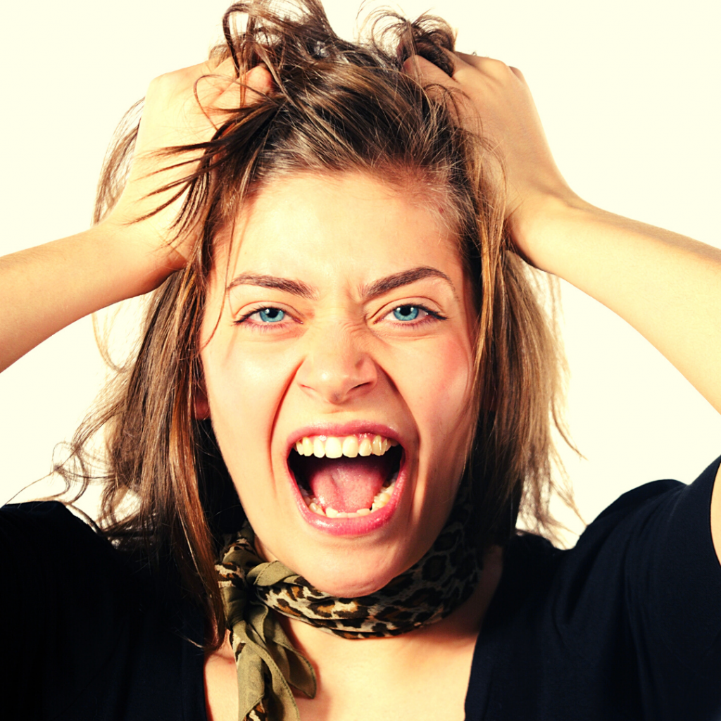 a woman pretending to pull her hair out in anger