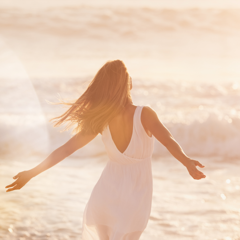 a woman in a white dress with her arms out walking along the ocean
