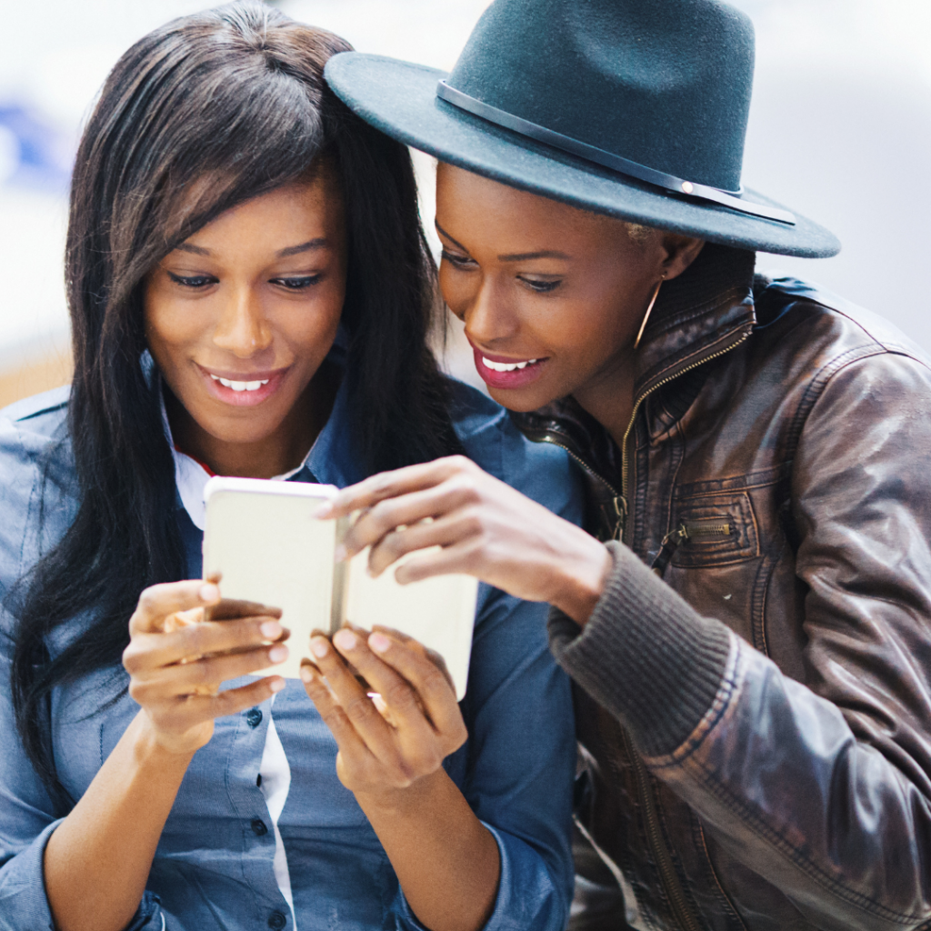 two women, one in a hat and one in a jacket, looking at something on a phone