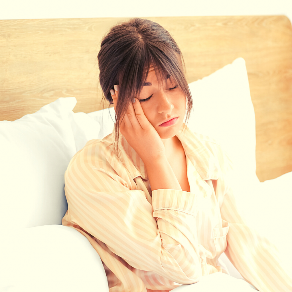 a brown haired woman looking exhausted in bed