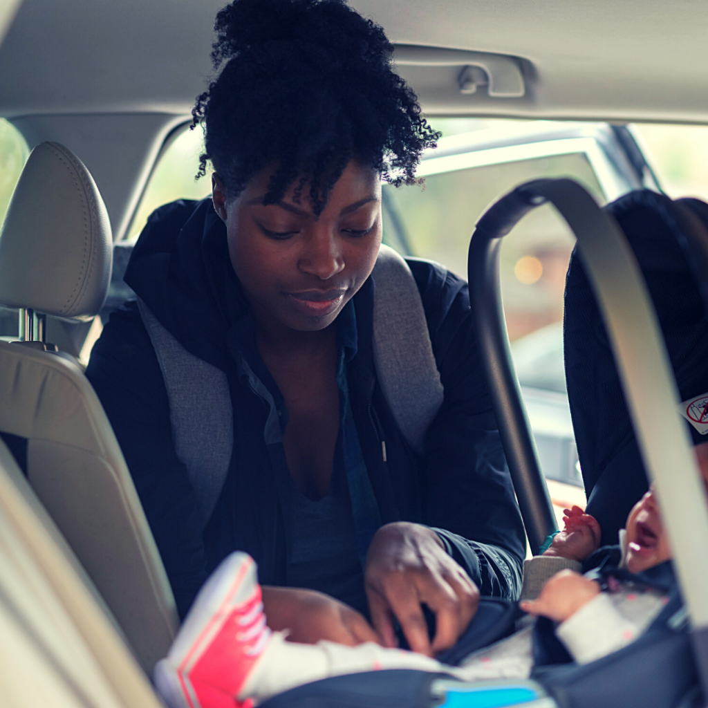 a woman trying to get her crying baby into their carseat in their car