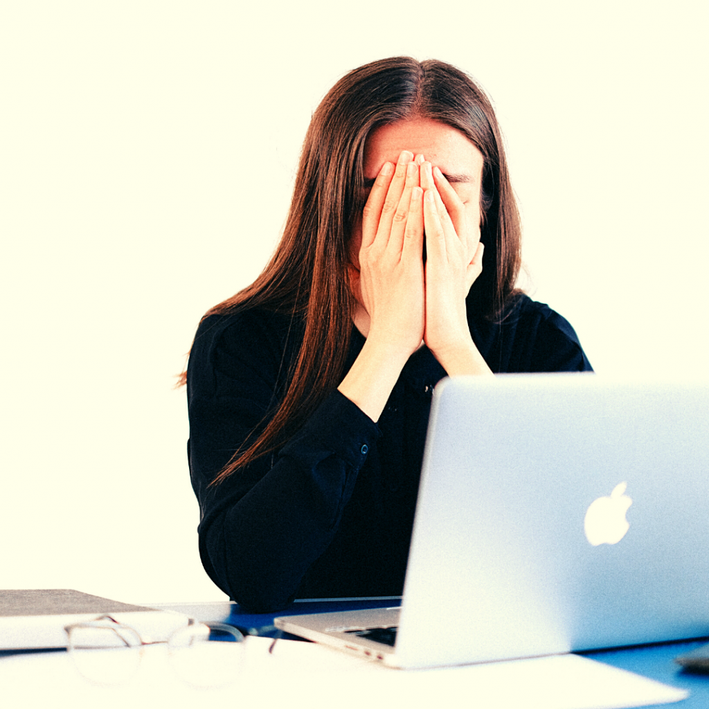 a woman holding her face in her hands while sitting in front of a laptop