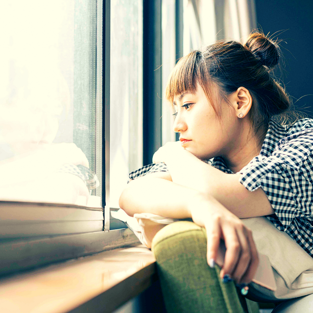 a woman in a plaid shirt looking out a window