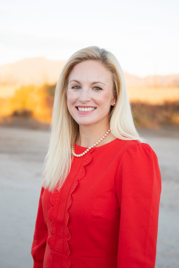 blonde lady smiling in red shirt and pearls