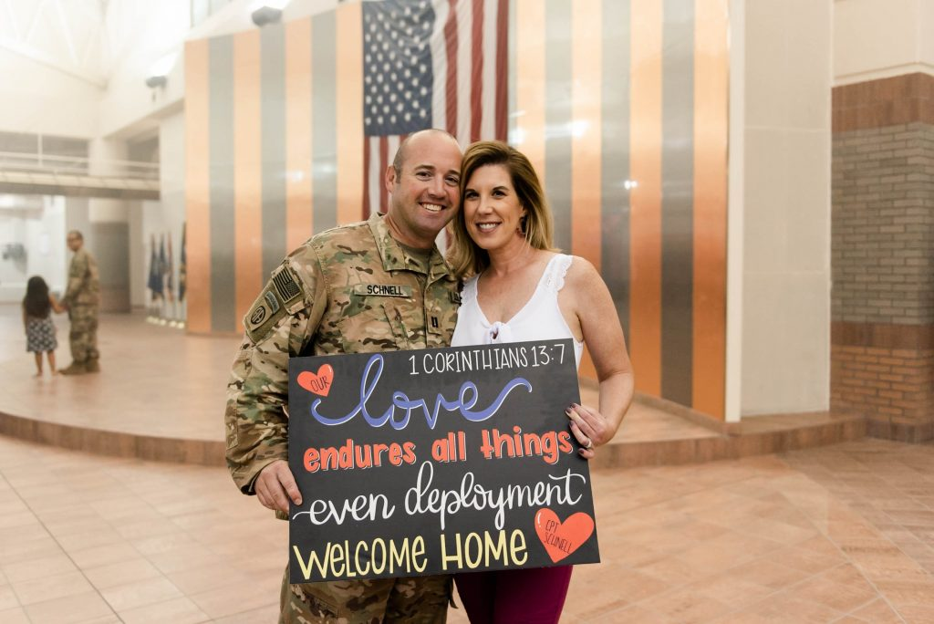 a man in a military uniform and woman couple holding a welcome home sign